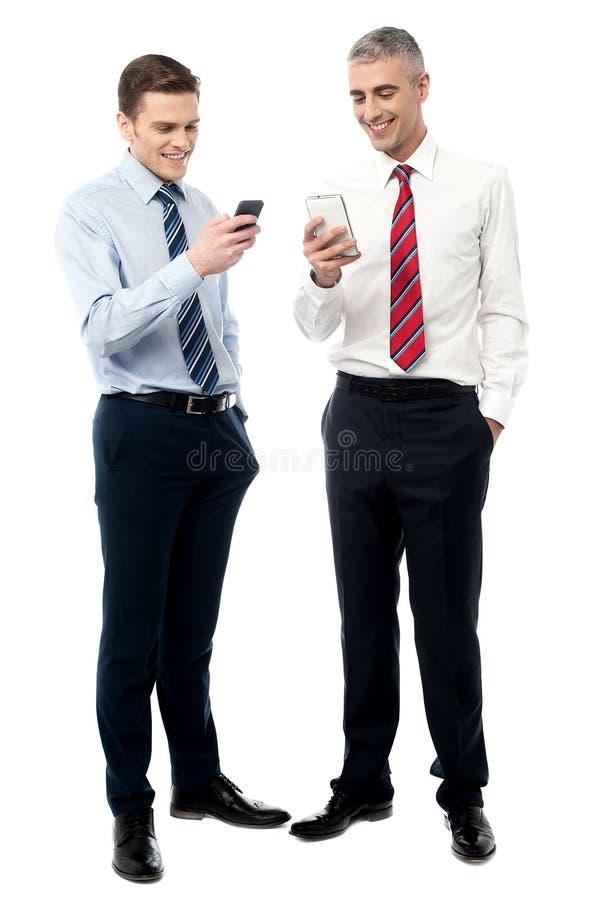 Ejecutivos jovenes que usan el teléfono móvil fotos de archivo libres de regalías