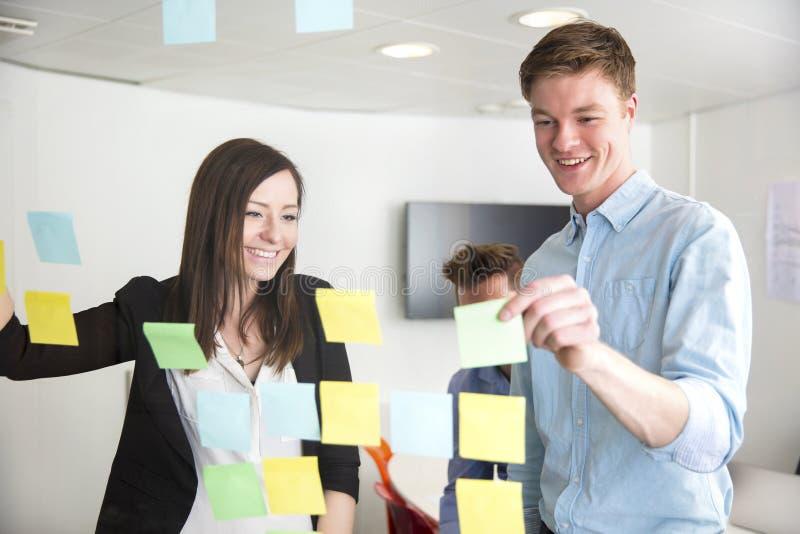 Ejecutivos que discuten sobre las notas pegadas en el vidrio en oficina imagen de archivo libre de regalías