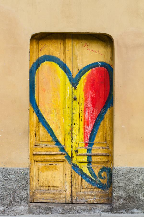 Ejemplo de la forma del corazón de la pintada en puerta de madera amarilla imagen de archivo
