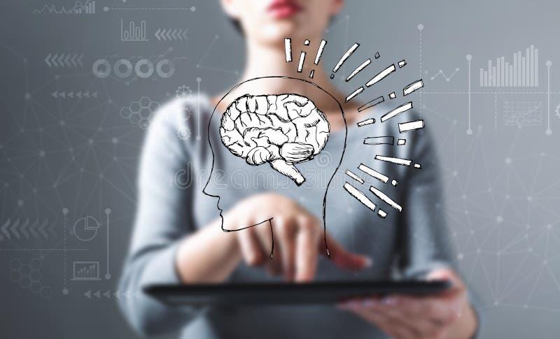 Ejemplo del cerebro con la mujer que usa una tableta fotos de archivo