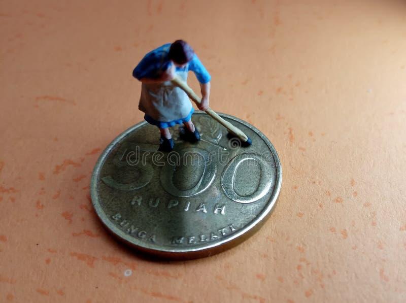 Ejemplo macro conceptual para la actividad del lavadero del dinero, mini figura monedas de oro limpia del trabajador de Indonesia fotos de archivo libres de regalías