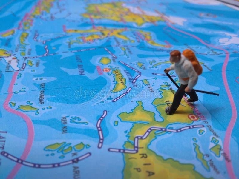 Ejemplo para el día de fiesta de la aventura, Mini Figure Hiker que camina en el atlas imagen de archivo libre de regalías