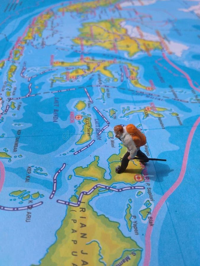 Ejemplo para el día de fiesta de la aventura, Mini Figure Hiker que camina en el atlas fotografía de archivo libre de regalías