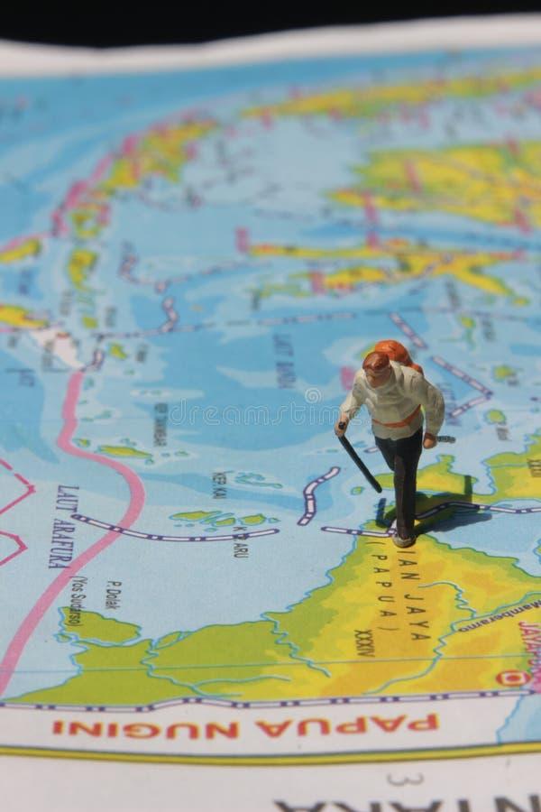 Ejemplo para el día de fiesta de la aventura, Mini Figure Hiker que camina en el atlas fotos de archivo