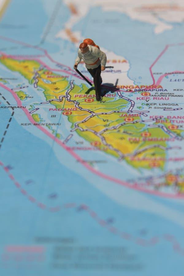 Ejemplo para el día de fiesta de la aventura, Mini Figure Hiker que camina en el atlas imagenes de archivo