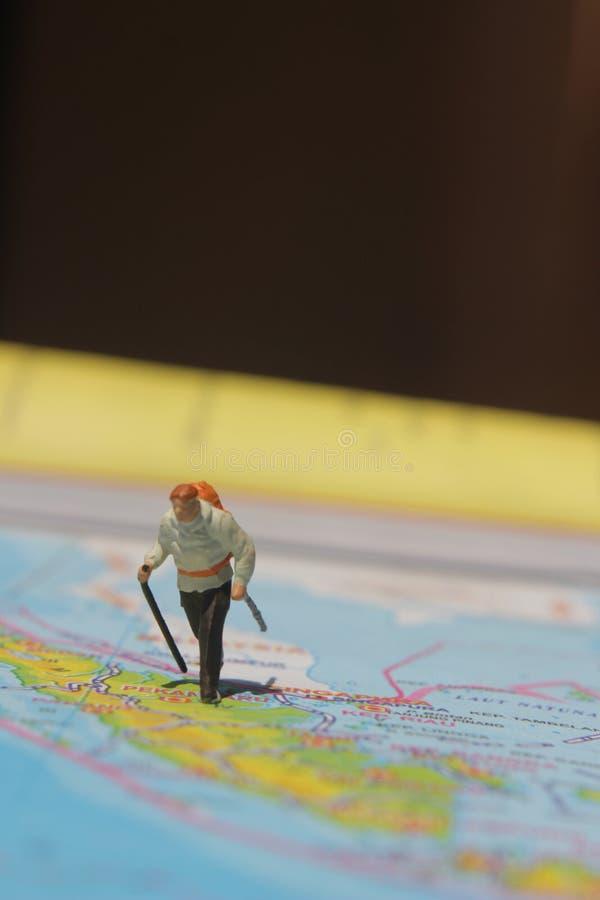 Ejemplo para el día de fiesta de la aventura, Mini Figure Hiker que camina en el atlas fotos de archivo libres de regalías