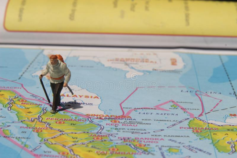 Ejemplo para el día de fiesta de la aventura, Mini Figure Hiker que camina en el atlas imágenes de archivo libres de regalías