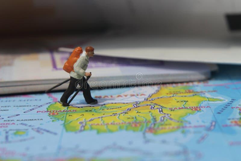 Ejemplo para el día de fiesta de la aventura, Mini Figure Hiker que camina en el atlas, pasando por el pasaporte grande foto de archivo libre de regalías