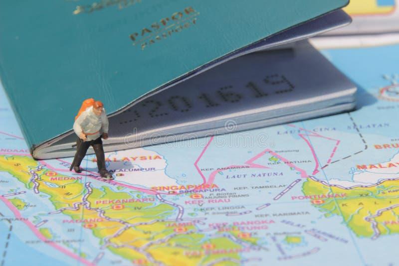 Ejemplo para el día de fiesta de la aventura, Mini Figure Hiker que camina en el atlas, pasando por el pasaporte grande fotografía de archivo libre de regalías