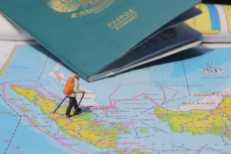 Ejemplo para el día de fiesta de la aventura, Mini Figure Hiker que camina en el atlas, pasando por el pasaporte grande foto de archivo