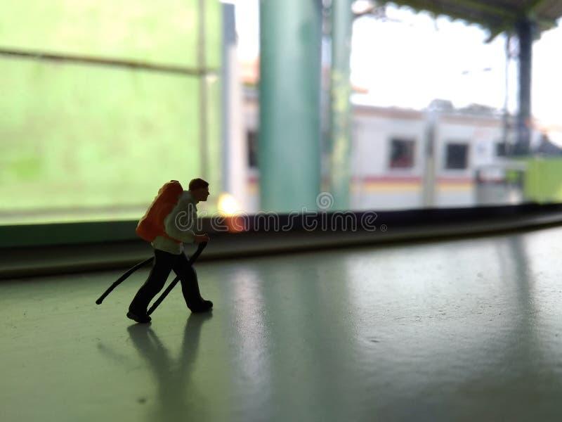 Ejemplo para el día de fiesta de la aventura, Mini Figure Hiker Walking en el tren Windows imagen de archivo