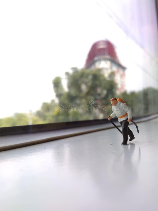 Ejemplo para el día de fiesta de la aventura, silueta Mini Figure Hiker Walking en el tren Windows foto de archivo