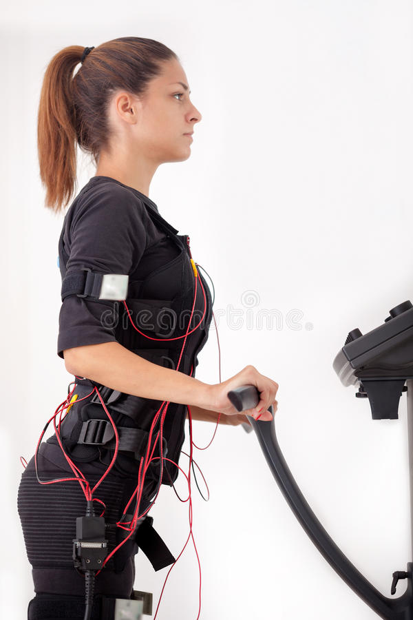Ejercicio apto de la mujer de los jóvenes en la electro máquina muscular del estímulo imagenes de archivo