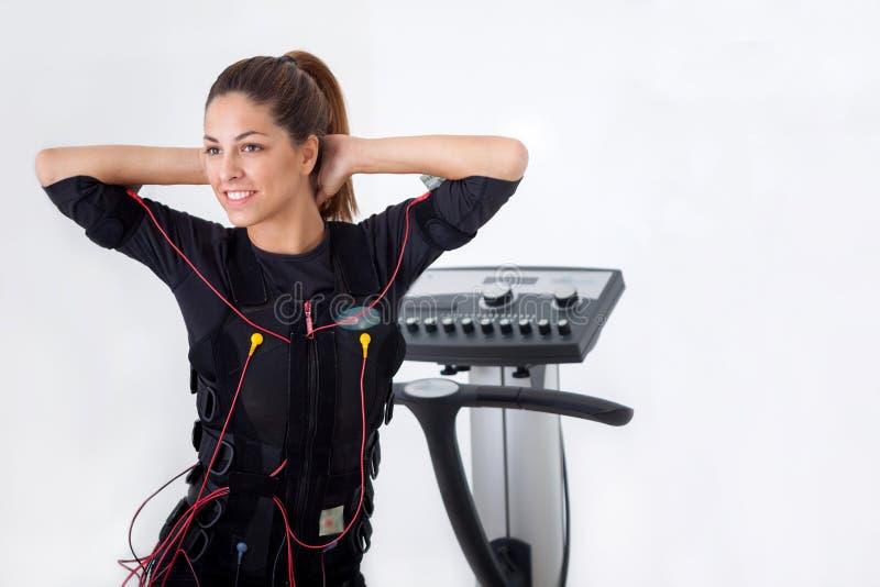 Ejercicio apto de la mujer de los jóvenes en la electro máquina muscular del estímulo fotografía de archivo libre de regalías