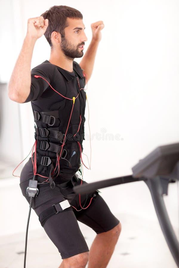 Ejercicio apto del hombre en la electro máquina muscular del estímulo imagenes de archivo
