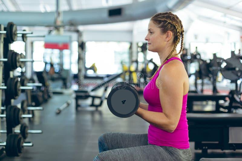Ejercicio atlético femenino con pesa de gimnasia en centro de aptitud fotografía de archivo libre de regalías