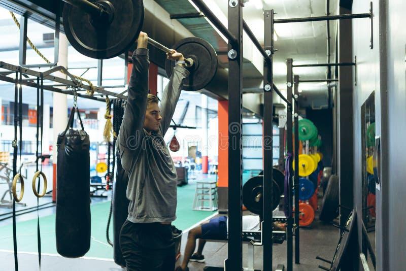 Ejercicio atlético masculino con el barbell en centro de aptitud foto de archivo