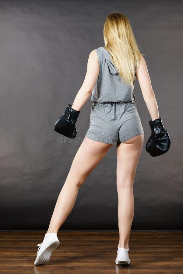 Ejercicio de la muchacha del boxeador con los guantes de boxeo imagen de archivo