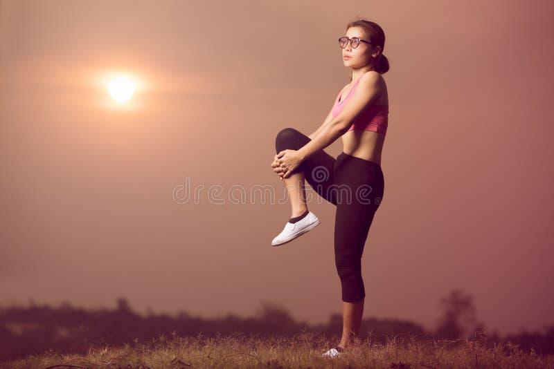 Ejercicio de la mujer con puesta del sol fotografía de archivo
