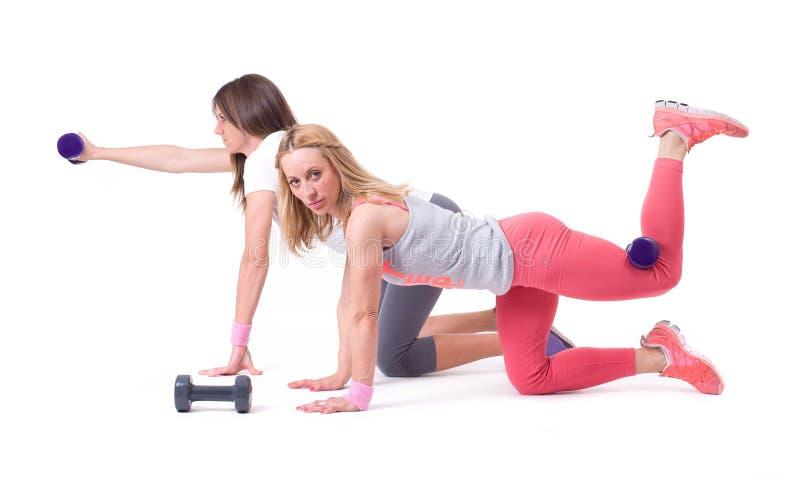 Ejercicio de la mujer de dos deportes con pesas de gimnasia fotografía de archivo