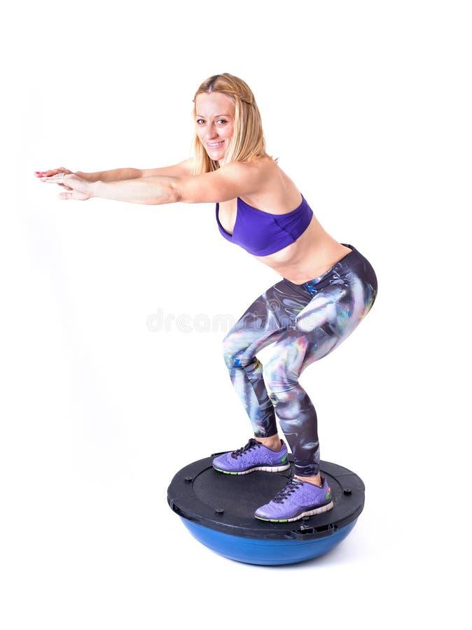 Ejercicio de la mujer del deporte con una bola de los pilates fotografía de archivo