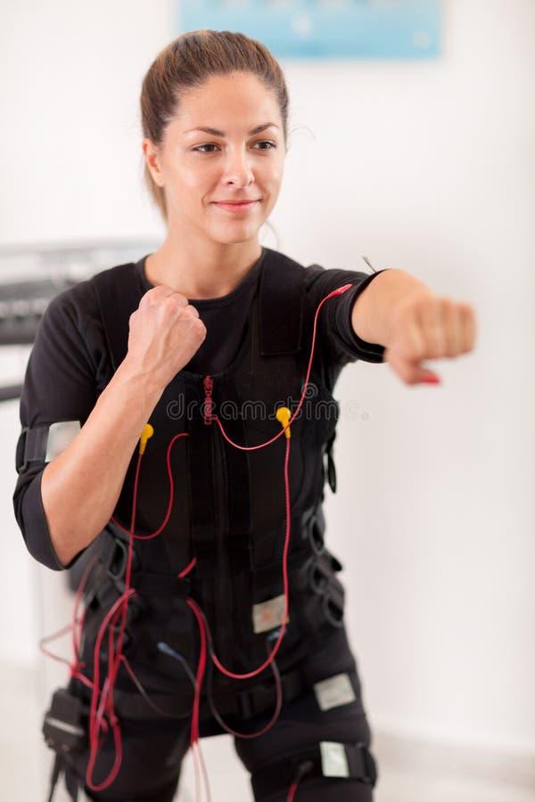 Ejercicio de la mujer joven en la electro máquina del estímulo foto de archivo