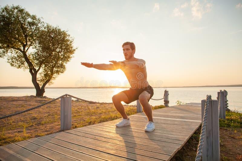 Ejercicio de la posición en cuclillas del aire del entrenamiento del hombre de la aptitud en la playa afuera Crossfit de ejercici foto de archivo