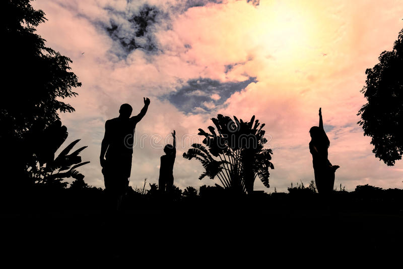 Ejercicio de la yoga de los hombres y de las mujeres de la silueta imagen de archivo libre de regalías