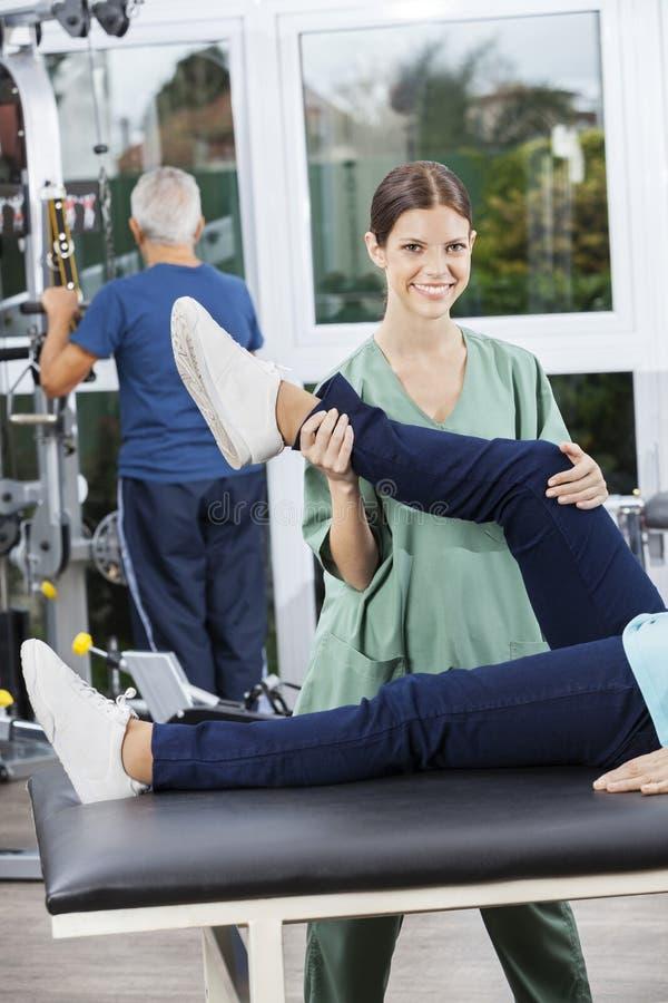 Ejercicio de pierna de Assisting Woman In de la enfermera en el centro de aptitud de la rehabilitación imagenes de archivo