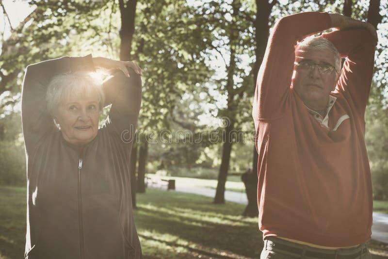 Ejercicio de relajación y de trabajo de los pares mayores junto en parque imagen de archivo