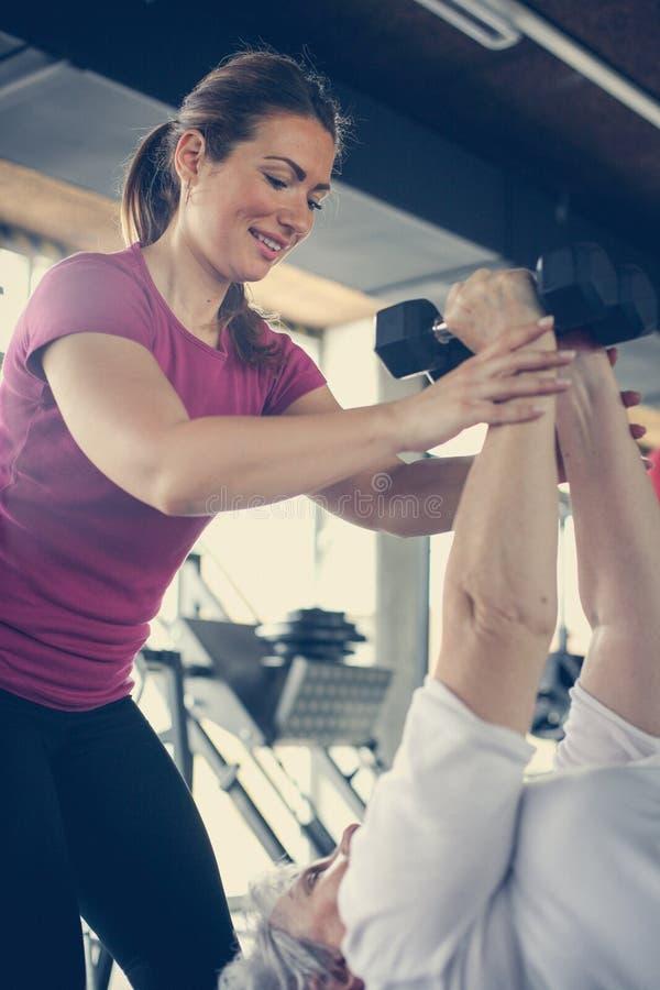 Ejercicio de trabajo del instructor con la mujer mayor en el gimnasio imagenes de archivo