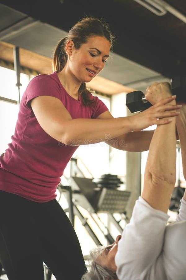 Ejercicio de trabajo del instructor con la mujer mayor en el gimnasio fotos de archivo libres de regalías