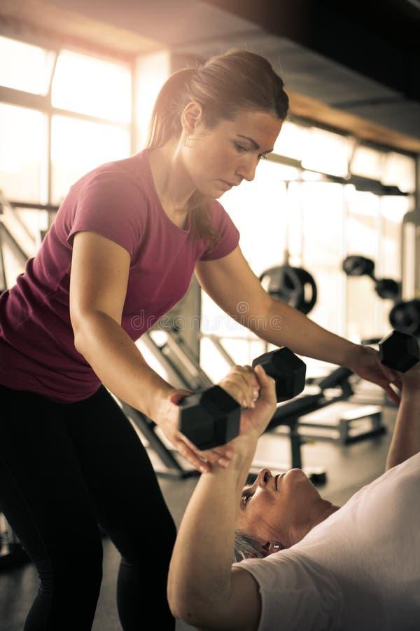 Ejercicio de trabajo del instructor con la mujer mayor en el gimnasio imagen de archivo libre de regalías