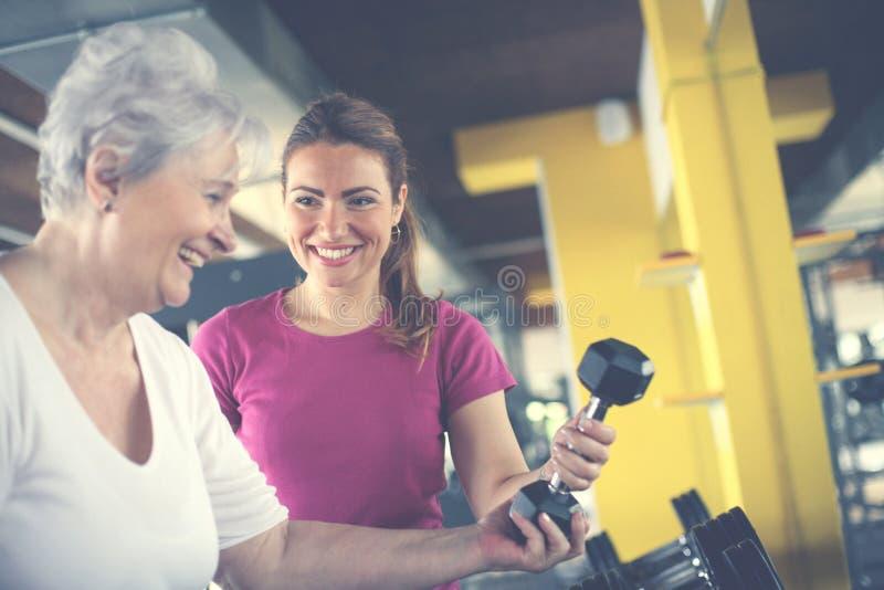 Ejercicio de trabajo del instructor con la mujer mayor en el gimnasio foto de archivo libre de regalías