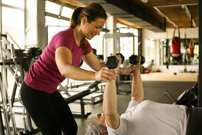 Ejercicio de trabajo del instructor personal con la mujer mayor en el gimnasio foto de archivo libre de regalías