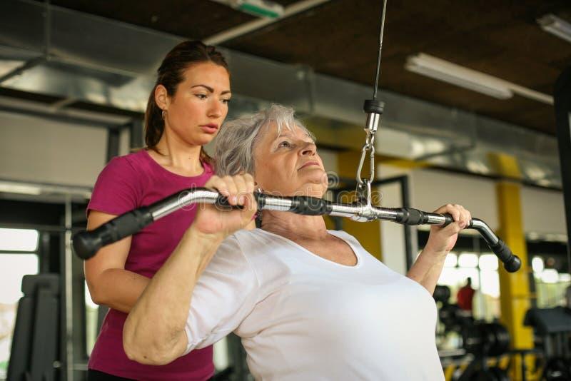 Ejercicio de trabajo de la mujer mayor activa en el gimnasio imagen de archivo