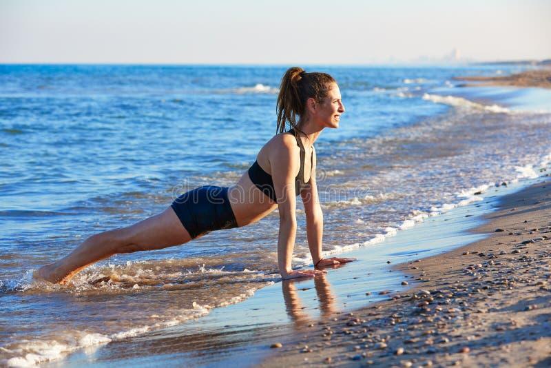 Ejercicio del entrenamiento de la yoga de Pilates al aire libre en la playa imagen de archivo