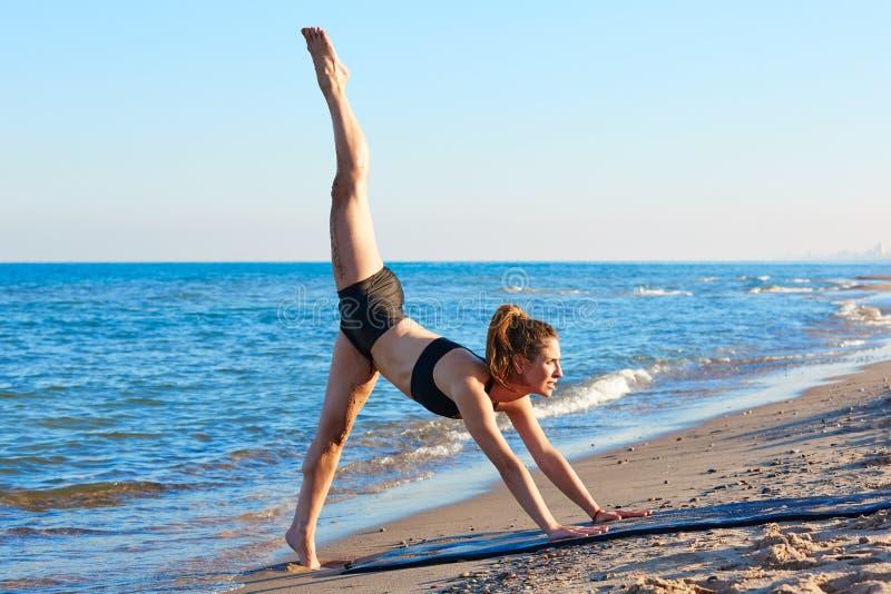Ejercicio del entrenamiento de la yoga de Pilates al aire libre en la playa fotografía de archivo