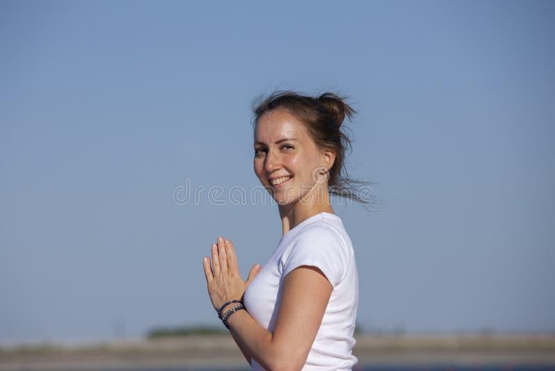 Ejercicio del entrenamiento de la yoga de Pilates al aire libre en el embarcadero del lago foto de archivo