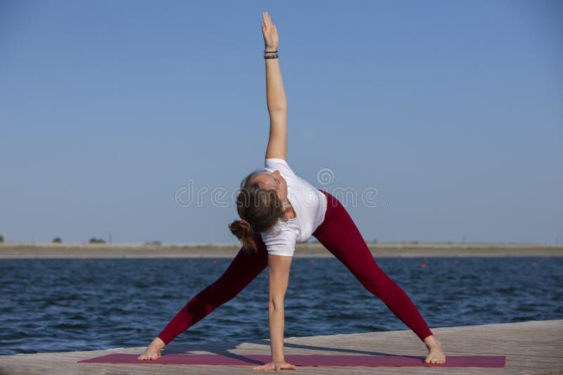 Ejercicio del entrenamiento de la yoga de Pilates al aire libre en el embarcadero del lago fotos de archivo