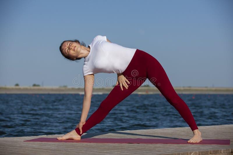 Ejercicio del entrenamiento de la yoga de Pilates al aire libre en el embarcadero del lago imagen de archivo