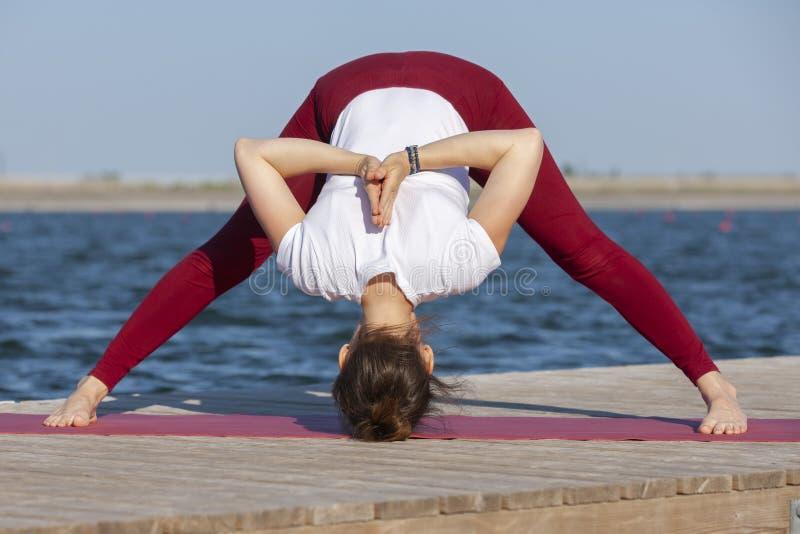 Ejercicio del entrenamiento de la yoga de Pilates al aire libre en el embarcadero del lago imagen de archivo libre de regalías