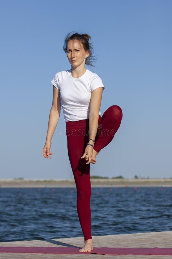Ejercicio del entrenamiento de la yoga de Pilates al aire libre en el embarcadero del lago fotos de archivo libres de regalías