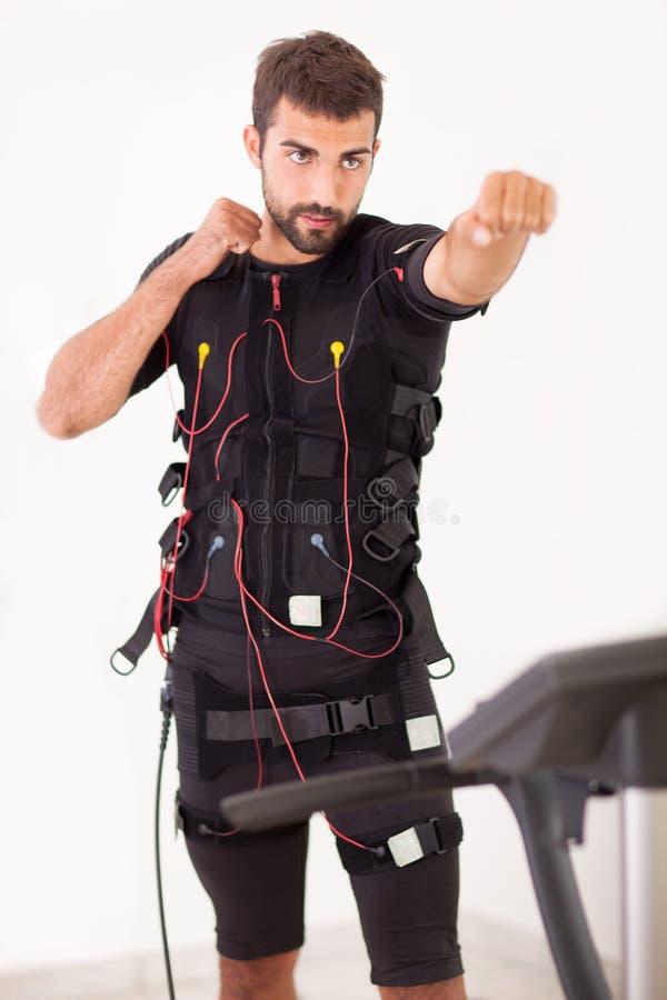 Ejercicio del hombre en la electro máquina muscular del estímulo imagen de archivo libre de regalías