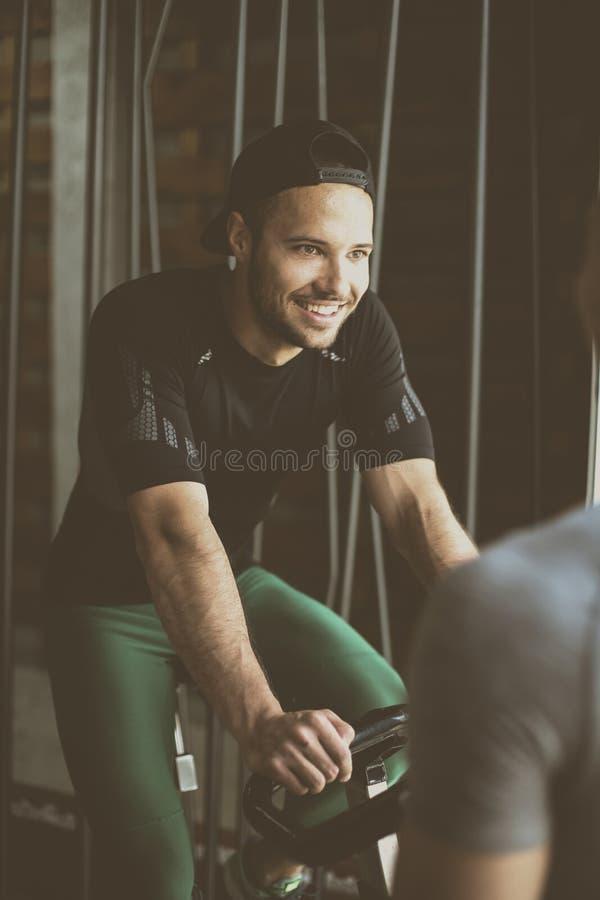 Ejercicio del hombre joven en las bicis inmóviles en clase de la aptitud fotografía de archivo