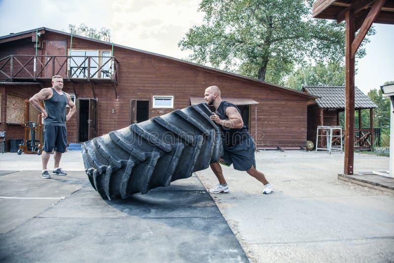 Ejercicio del tirón del neumático Contratan al deportista calvo a entrenamiento con el neumático pesado en gimnasio de la calle C fotos de archivo