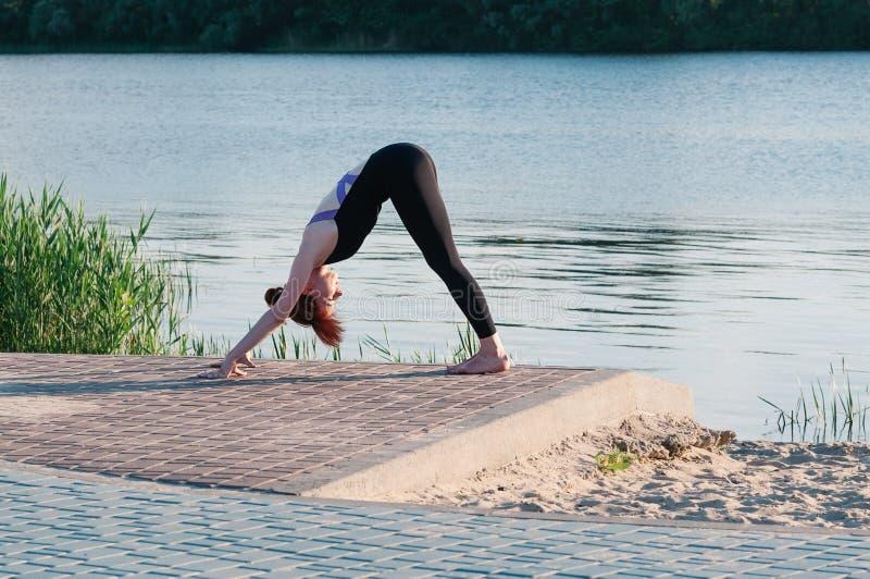 Ejercicio femenino bonito apto de la yoga de la pr?ctica al aire libre fotos de archivo