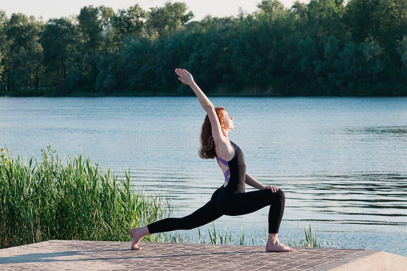 Ejercicio femenino bonito apto de la yoga de la pr?ctica al aire libre foto de archivo