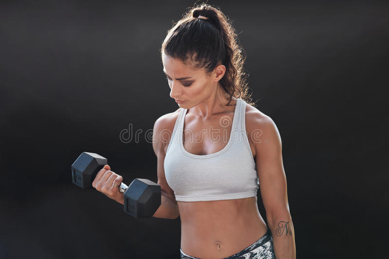 Ejercicio femenino fuerte y muscular con pesa de gimnasia foto de archivo libre de regalías