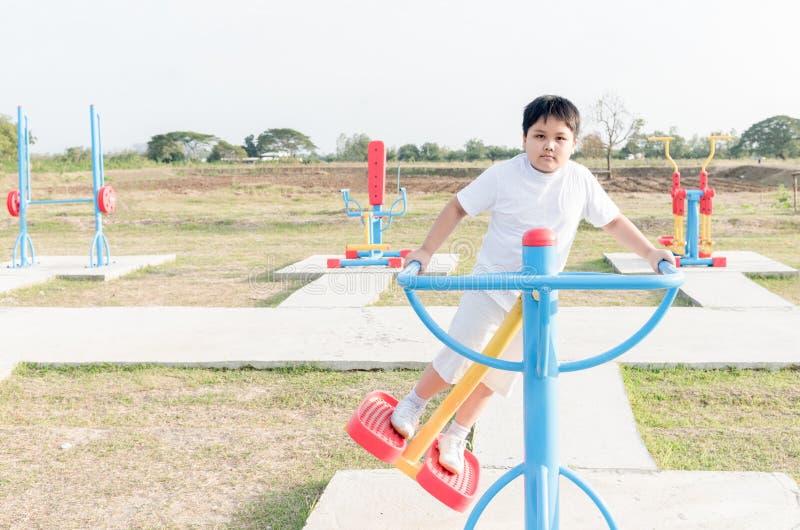 Ejercicio gordo obeso del muchacho en el parque de la salud pública foto de archivo